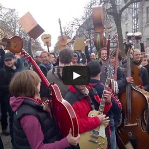 Musiker stehen auf der Straße und halten ihre Instrumente in die Höhe.