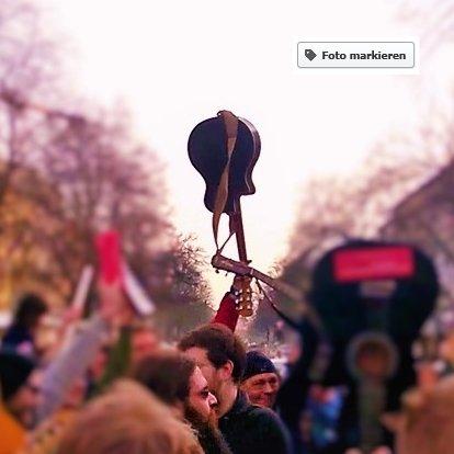 Jemand hält eine Gitarre am Griffbrett fest und stemmt sie in die Höhe (fast malerisch, große Symbolik, Protest, musikalische Machtergreifung)